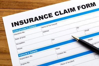 Insurance claim form on table with pen